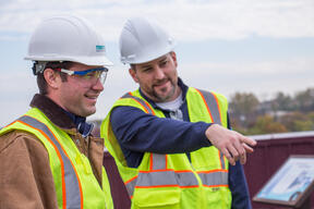 Two construction workers look at project